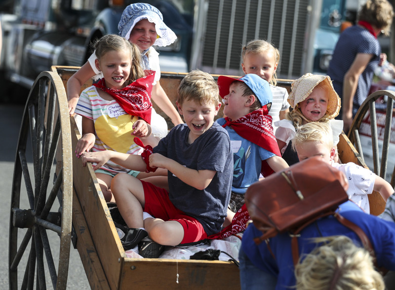 Children laugh as the handcart they are riding is set down during the 65th annual Grand Parade along Main Street in Bountiful on Friday, July 20, 2018.