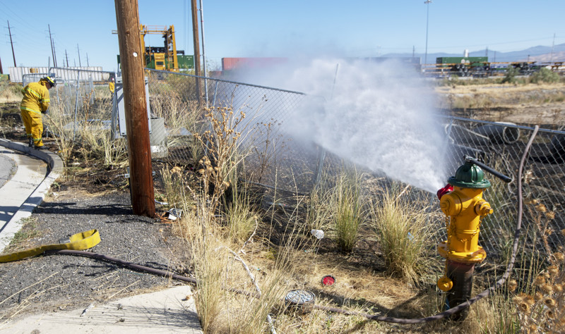 Salt Lake City firefighters mop up after a small fire near the train tracks at 1000 South and 4800 West on Tuesday, Aug. 28, 2018.