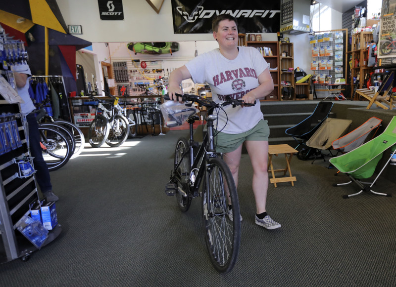 Megan Averill picks up her bike from Andrew Wagstaff after getting a new chain at Wasatch Touring in Salt Lake City on Monday, May 13, 2019. Her new bike chain was made in China, and bike parts from China could be impacted by tariffs.
