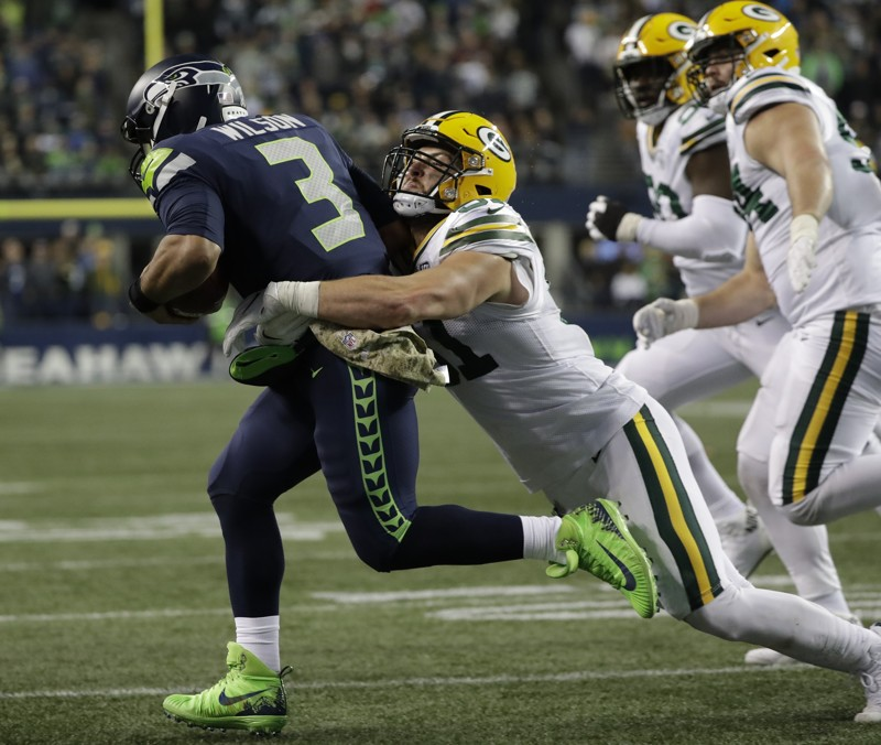 Seattle Seahawks quarterback Russell Wilson is tackled by Green Bay Packers linebacker Kyler Fackrell during the second half of an NFL football game, Thursday, Nov. 15, 2018, in Seattle.