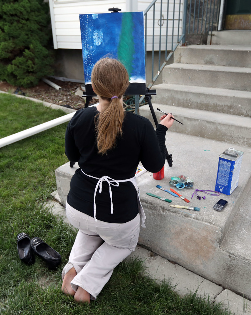 Christine, who struggles with anxiety, paints outside of her home in Murray on Friday, May 18, 2018. Painting helps her express her emotions.