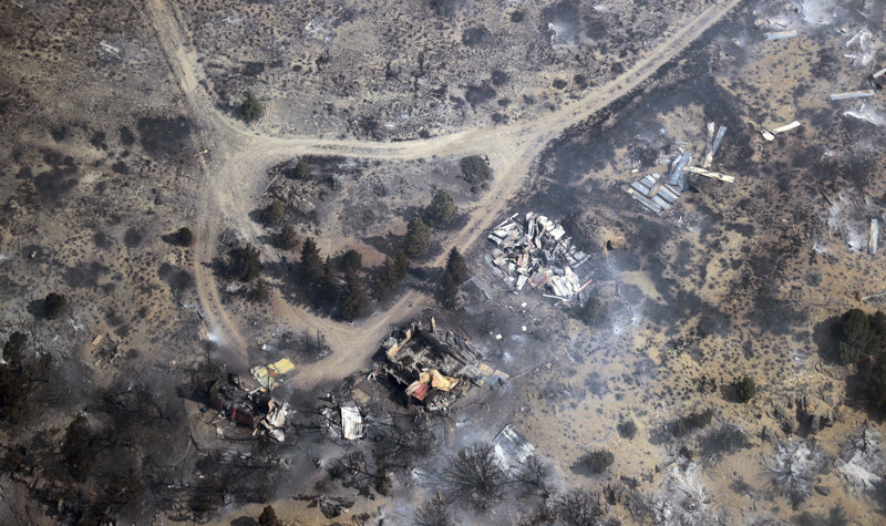 FILE - In this aerial photo, burned down structures are seen as a wildfire continues to burn east of Strawberry Reservoir, in Wasatch County, Utah, on Tuesday, July 3, 2018.