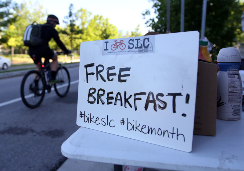 A biker cruises past a SLCMoves pit stop that offers free breakfast and swag for bike commuters in Salt Lake City on Tuesday, May 15, 2018.