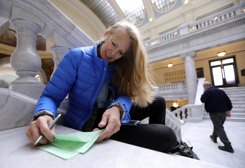 Janée Gillette, physicians assistant, writes notes to her representatives in support of Prop. 2 before a special session of the Utah State Legislature at the Capitol in Salt Lake City on Monday, Dec. 3, 2018.