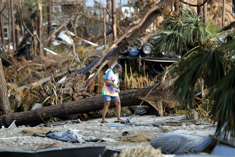 Roxie Cline picks up items in the vicinity of her destroyed motor home that she lived in, in the aftermath of Hurricane Michael in Mexico Beach, Fla., on Wednesday, Oct. 17, 2018.