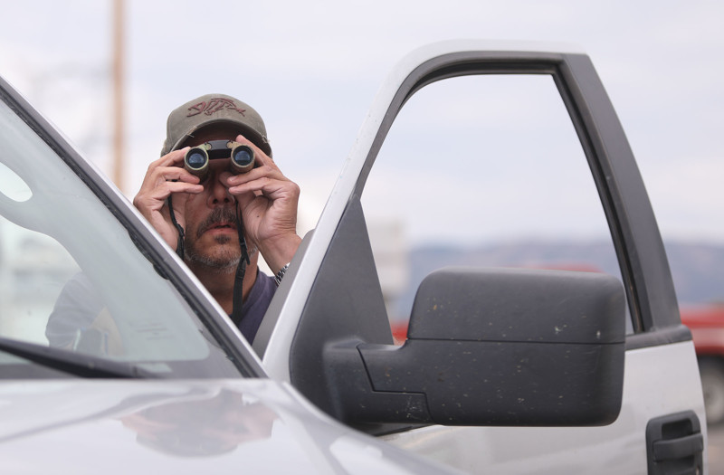 Doug Adams uses binoculars to look for his house from the parking lot of and LDS church in Fruitland on Wednesday, July 11, 2018. Adams' house was destroyed in the Dollar Ridge Fire.