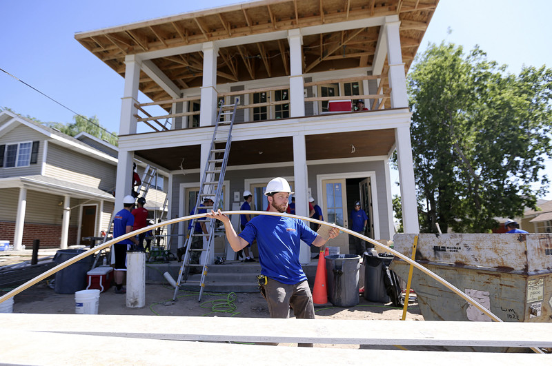 Volunteers, builders and contractors work on a home being built by HGTV's