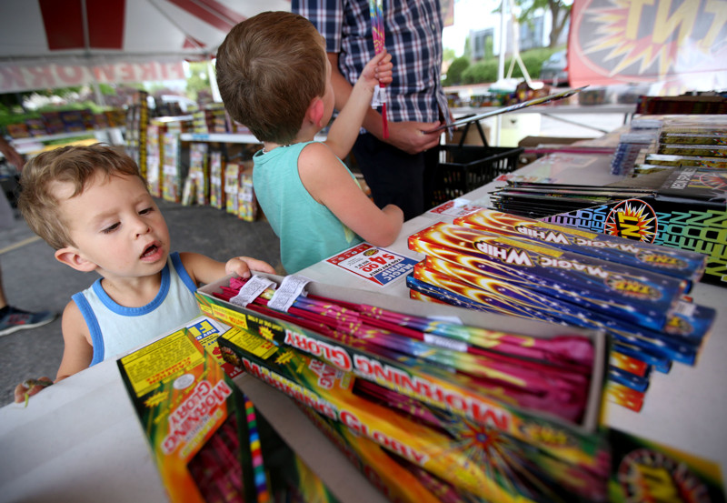 Emerson Mangelson looks at Morning Glory sparklers while shopping for fireworks with his brother and father at a TNT stand in Salt Lake City on Tuesday, July 3, 2018.