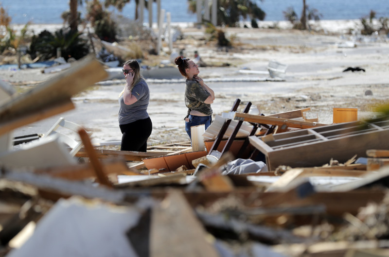Christina Amanda, right, and Connie Huff wait for an insurance adjuster as they look for their possessions at the site of their destroyed home in the aftermath of Hurricane Michael in Mexico Beach, Fla., on Wednesday, Oct. 17, 2018.