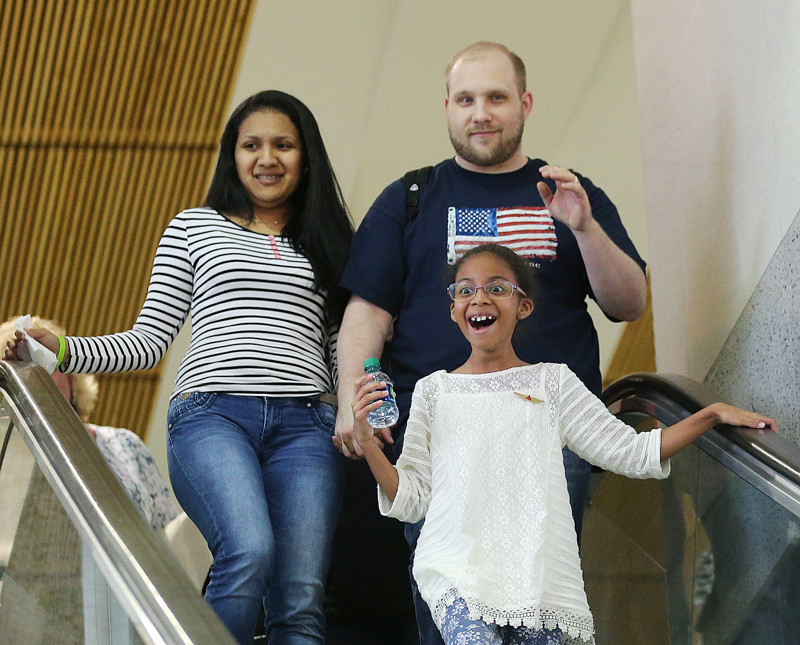 Josh Holt and his wife Thamy and one of their daughters Marian Leal react as are family and friends cheer as they arrive at the International terminal of the Salt Lake City International airport on Monday, May 28, 2018.