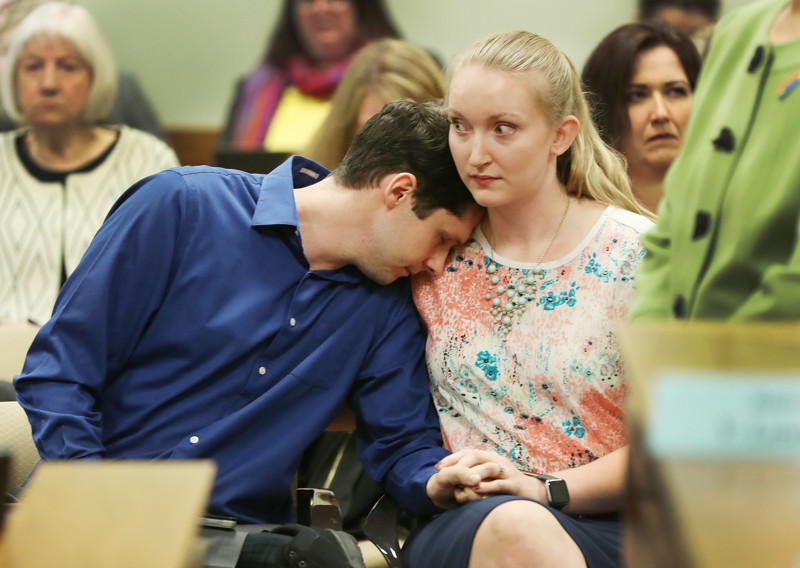 FILE - Caleb sits with his wife Julia after both testified during a House Judiciary Committee hearing at the Capitol in Salt Lake City on Tuesday, March 5, 2019 regarding HB0399 which would prohibit the practice of conversion therapy upon minors. Caleb went through conversion therapy.