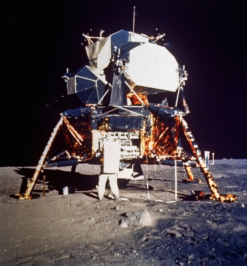 Astronaut Edwin E. Aldrin Jr., lunar module pilot, prepares to deploy the Early Apollo Scientific Experiments Package (EASEP) during Apollo 11 lunar surface extravehicular activity, July 20, 1969. Astronaut Neil A. Armstrong, commander, took this photograph with a 70 mm lunar surface camera. Aldrin is removing the EASEP from its stowed position.