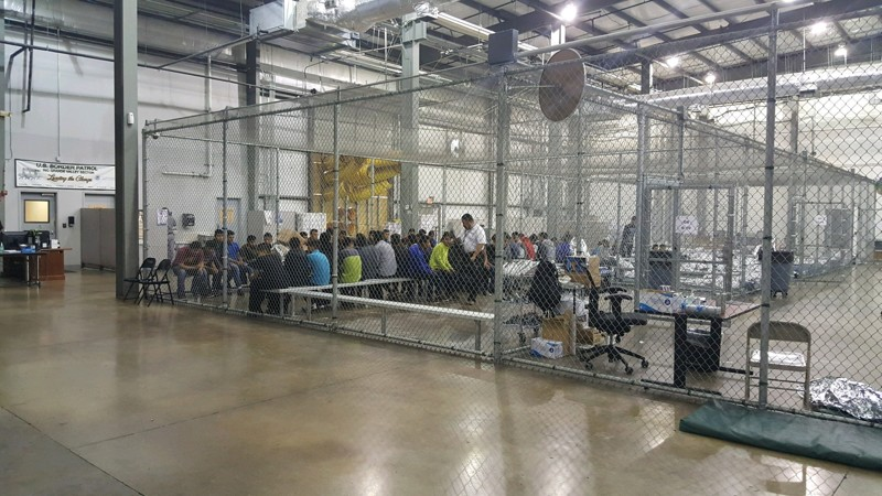 The warehouse-like facility has holding pens made from chain-link fences on the inside separating the immigrants.