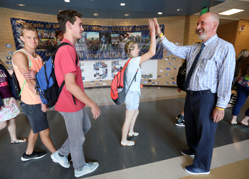 Students high-five Salem Hills High School Principal Bart Peery as they walk by in the high school's hallways on Thursday, May 24, 2018.