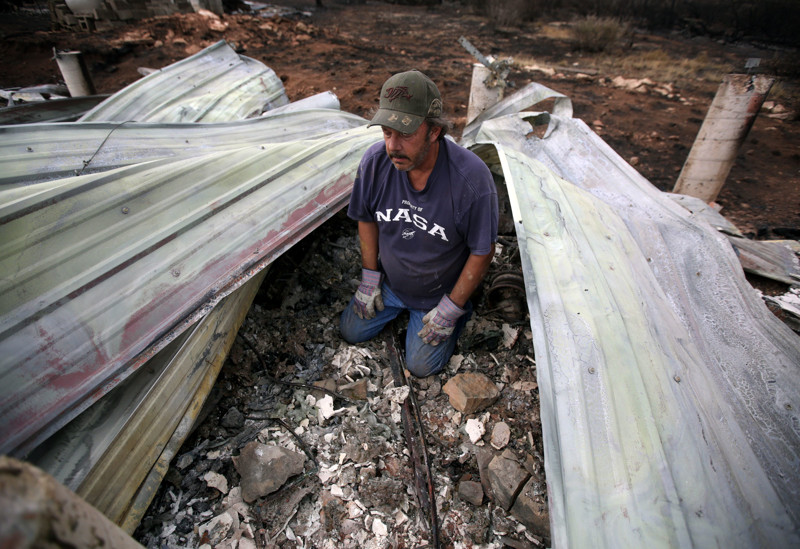 Doug Adams takes a break while looking through the rubble of his Fruitland house for an old broken boat propeller that has sentimental value on Wednesday, July 11, 2018. The house was destroyed in Dollar Ridge Fire.