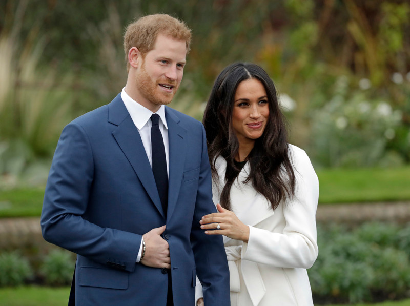 In this Monday Nov. 27, 2017 file photo, Britain's Prince Harry and his fiancee Meghan Markle pose for photographers in the grounds of Kensington Palace in London. The couple will celebrate their wedding Saturday, May 19.