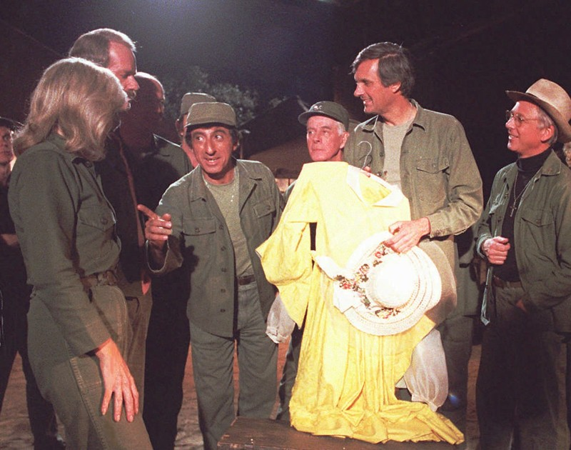 """Members of the """"M\*A\*S\*H"""" cast gather around to bury Klinger's yellow dress in a foot-locker time capsule during taping of the show's final episode in January 1983. The 2 1/2-hour finale was the highest-rated television show in Nielsen Media Research until the 2010 Super Bowl finally topped it. From left, are cast members Loretta Swit, Mike Farrell, Jamie Farr, Harry Morgan, Alan Alda and William Christopher."""