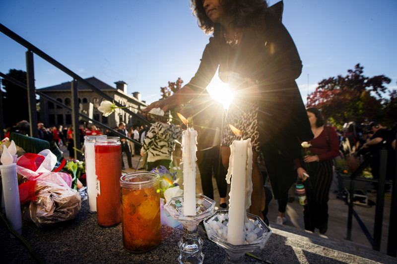 Those attending the vigil for University of Utah student-athlete Lauren McCluskey place flowers, cards and candles on the steps of the Park Building at the University of Utah in Salt Lake City on Wednesday, Oct. 24, 2018. McCluskey was killed Monday, Oct. 22, 2018.