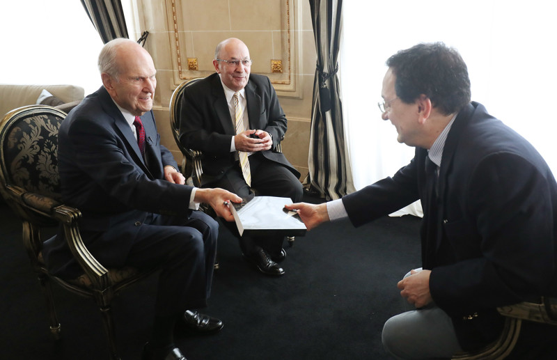 President Russell M. Nelson of The Church of Jesus Christ of Latter-day Saints, left, gives a copy of his biography to Sergio Rubin, Argentine journalist and biographer of Pope Francis, after an interview in Montevideo, Uruguay on Oct. 26, 2018. Carlos Aguero, center, interprets.
