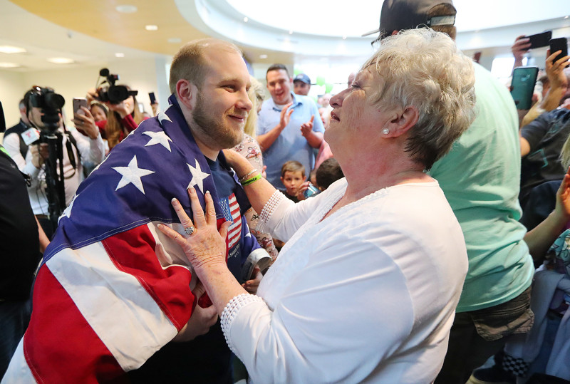 Josh Holt's grandmother Linda Holt drapes an American flag around him as he and his wife Thamy are swarmed by family and friends at the International Terminal in Salt Lake City International Airport on Monday, May 28, 2018.