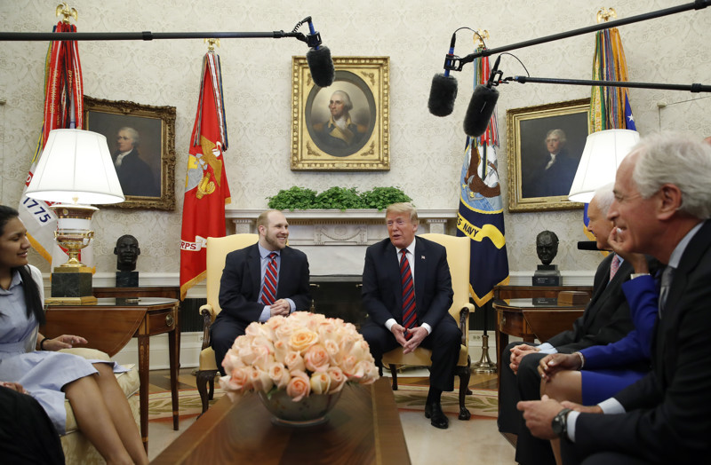 President Donald Trump, right, talks with Joshua Holt, who was recently released from a prison in Venezuela, in the Oval Office of the White House, Saturday, May 26, 2018, in Washington.