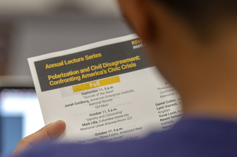 A student looks over Arizona State's annual lecture series on Thursday, Aug. 16, 2018, during a