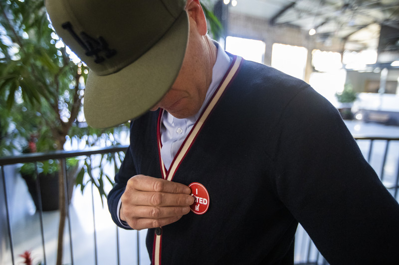 "Greg Walker puts on his ""I Voted"" sticker after voting at a polling station at Trolley Square in Salt Lake City on Tuesday, Nov. 6, 2018."