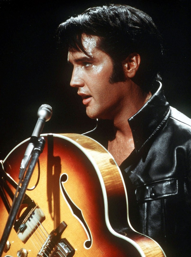 In this 1968 file photo, Elvis Presley holds his semi-acoustic guitar during a concert.