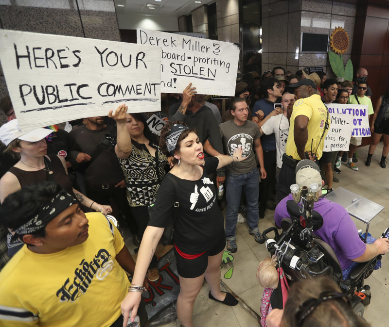 Protesters block the path of a security guard at the Chamber of Commerce Building at 175 E. 400 South in Salt Lake City on Tuesday, July 9, 2019. The protest over the Utah Inland Port began at the City-County Building and moved to the Chamber of Commerce Building where the port authority meets.