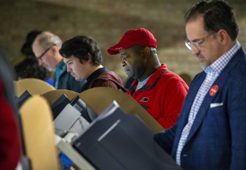 James Montgomery joins with other voters in casting their ballots at a polling station at Trolley Square in Salt Lake City on Tuesday, Nov. 6, 2018.