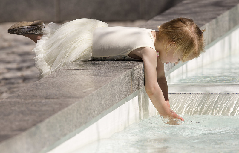 Four-year-old Katrina Christensen plays in the water near the reflecting pond during the Sunday afternoon session of the 188th Annual General Conference of The Church of Jesus Christ of Latter-day Saints on Sunday, April 1, 2018.