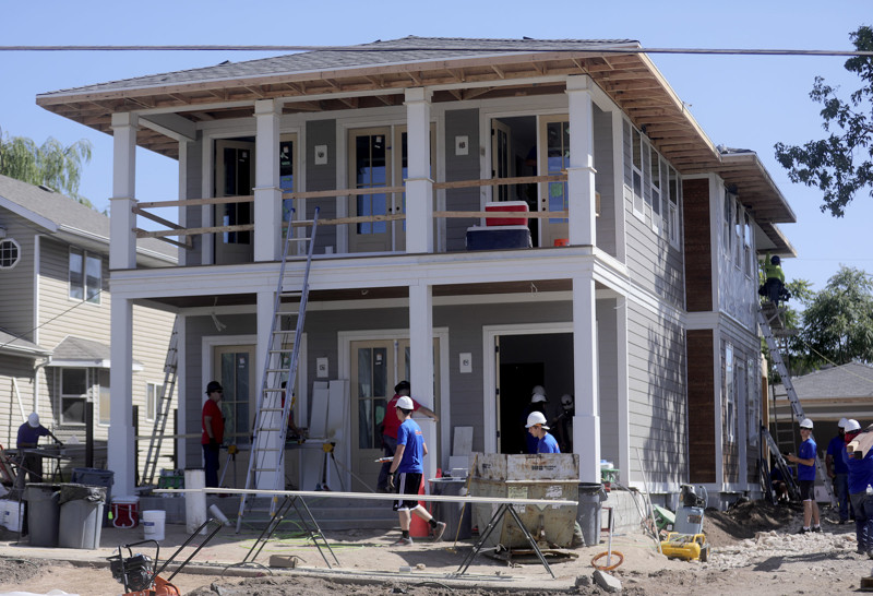 Builders, contractors and volunteers work on a home being built by HGTV's