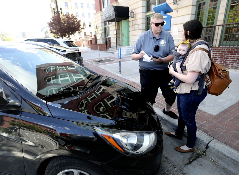 Wayne Howcroft, a Salt Lake City parking enforcement officer, talks to Jennifer Bean, who is holding daughter Molly, about mandatory reverse-in parking on 200 South in Salt Lake City on Wednesday, April 24, 2019. Howcroft gave Bean a warning instead of a ticket.