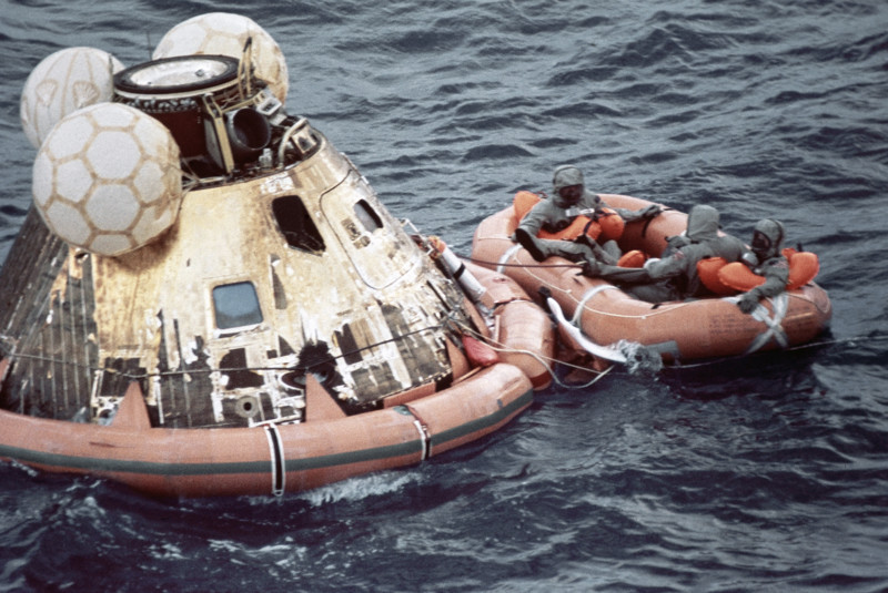U.S. Navy personnel, protected by Biological Isolation Garments, are recovering the Apollo 11 crew from the re-entry vehicle, which landed safely in the Pacific Ocean on July 24, 1969, after an eight-day mission on the moon.