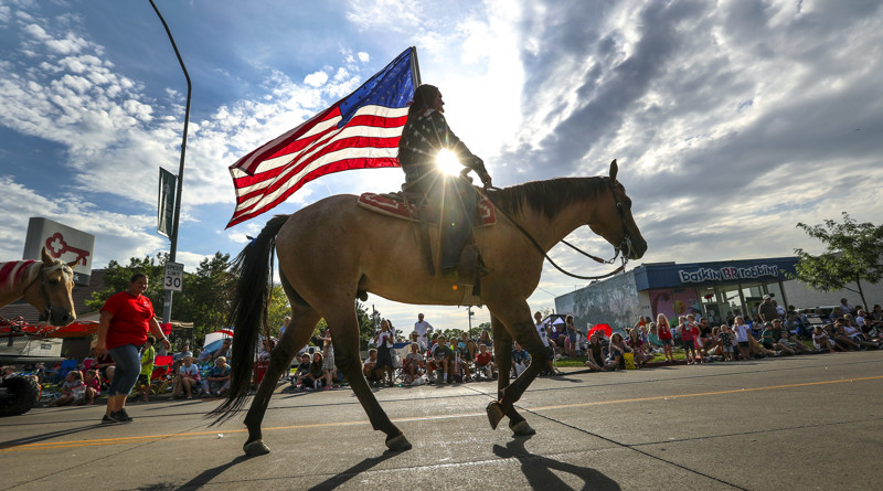 Elena Limon from the Cross E Ranch carries the American Flag during the 65th annual Grand Parade along Main Street in Bountiful on Friday, July 20, 2018.