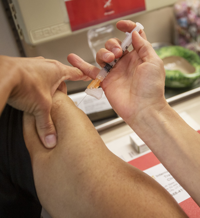 Holly Birich, manager of the Salt Lake County Health Department's International Travel Clinic in Salt Lake City, vaccinates a patient on Tuesday, July 30, 2019, prior to his trip overseas.