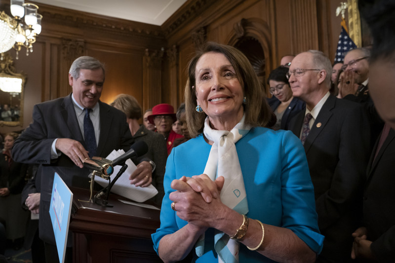 Speaker of the House Nancy Pelosi, D-Calif., joined at left by Sen. Jeff Merkley, D-Ore., smiles as she and fellow Democrats applaud the introduction of The Equality Act, a comprehensive nondiscrimination bill for LGBT rights, at the Capitol in Washington, Wednesday, March 13, 2019. (AP Photo/J. Scott Applewhite)