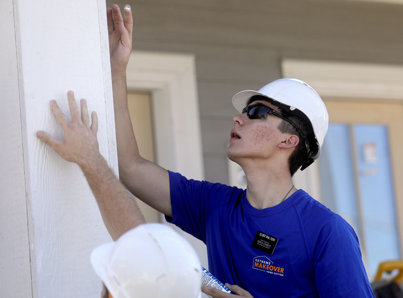 "Elder Dakota Walters, a missionary for The Church of Jesus Christ of Latter-day Saints, works with other volunteers on a home being built by HGTV's ""Extreme Makeover: Home Edition,"" in Ogden on Monday, Aug. 12, 2019. The house will be given to Anifah Barobi and her family, including her nephew Ashraf Kambere. Barobi, her daughter, Kambere, and his siblings were reunited at a refugee camp in Uganda after fleeing the Democratic Republic of the Congo where Kambere's parents were murdered. After years in the refugee camp, they were all relocated to Utah together."