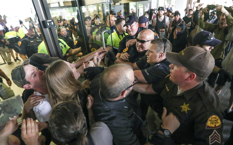 Salt Lake police and Utah Highway Patrol troopers force protesters out of the Chamber of Commerce Building at 175 E. 400 South in Salt Lake City on Tuesday, July 9, 2019. The protest over the Utah Inland Port began at the City-County Building and moved to the Chamber of Commerce Building where the port authority meets.