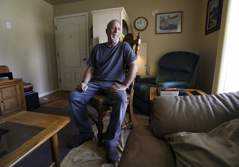 John Balaich sits on an antique chair in his living room in Washington Terrace, Weber County, on Monday, July 8, 2019. Because of an unpaid medical debt, Balaich could have lost some of his possessions including furniture and computers.